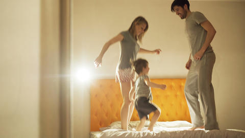 Happy family with little son dancing on bed at home in the evening before Footage