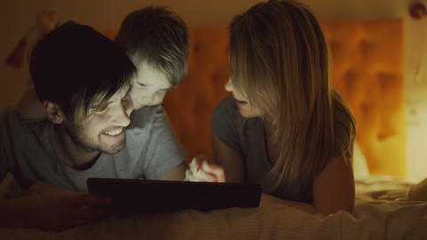 Happy family with little son using tablet computer and talking lying in bed at Footage