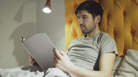 Young father reading book while his little son jumping on bed before sleeping in Footage