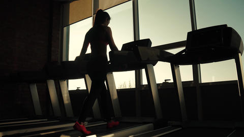 silhouette of a girl on a treadmill. young woman walks on a treadmill at the gym Footage
