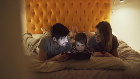 Happy family with little son a lying in bed at home and using tablet computer Photo