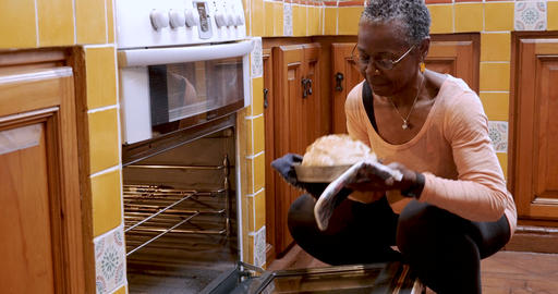 African American mature woman opens oven, removes fresh loaf of bread, and Footage