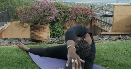 Flexible senior African American woman in her 60s doing sitting yoga poses and Footage