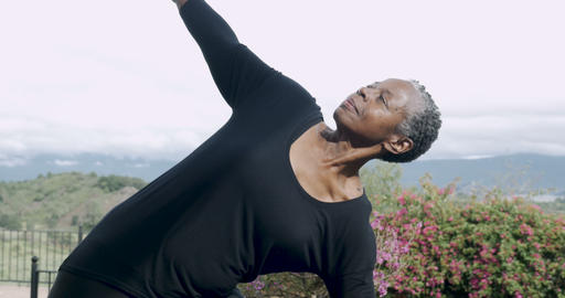 Attractive fit African American woman in 60s practicing yoga triangle pose Footage