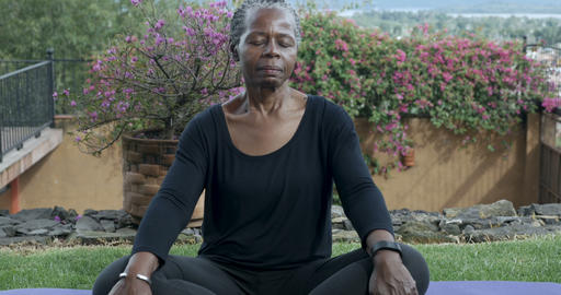 Push out of an attractive African American senior woman in her 60s meditating Footage
