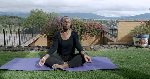 Healthy African American senior in 60s sitting cross legged meditating outside Footage