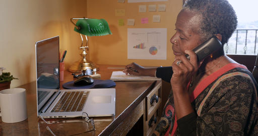 Happy smiling mature black woman talking and hanging up her cordless phone at Footage