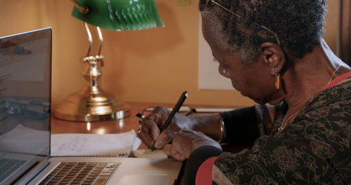Mature professional black woman writing reminders on yellow sticky notes and Live Action