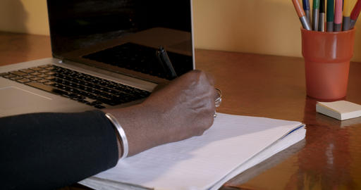Close up of a mature African American woman writing in a notebook next to her Footage