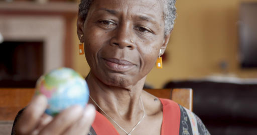 Happy smiling African American mature woman over 50 looking a world globe for Footage
