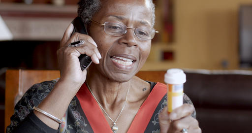 Happy black senior woman refilling her prescription to a pharmacy or talking to Footage