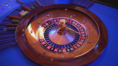 Roulette wheel - groupier spins the wheel - ball lands on field 14 red Live Action