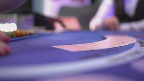 Gambling Black Jack in a casino - dealer spreading cards on a black jack table Live Action