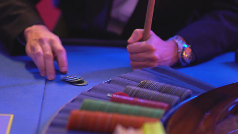 Roulette table in a casino - groupier grabs gaming tokens Live Action