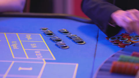 Roulette table in a casino - groupier prepares win pay out Live Action