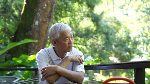 Asian senior guy thinking and worry in green lush nature background Live Action