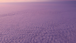 Window view from a plane reflecting sunset rays in purple and pink Image