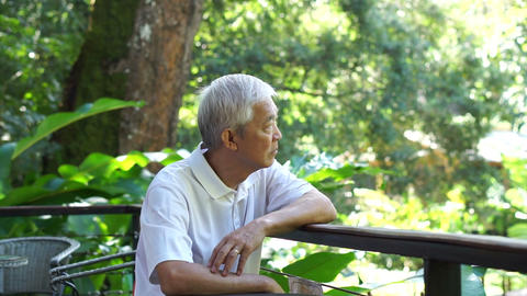 Asian senior guy thinking and worry in green lush nature background Footage