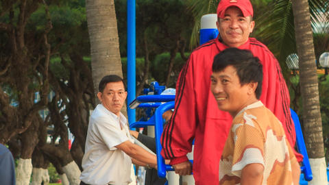 Men Do Morning Exercises On Simulators In City Park In Vietnam stock footage