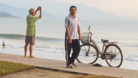 OLd Man Does Morning Exercises on Beach by Bike in Vietnam Footage