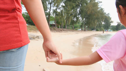 4K Slow motion mother and daughter walking hand in hand on the beach Footage