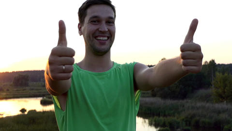 Young man showing thumbs up at sunset Footage