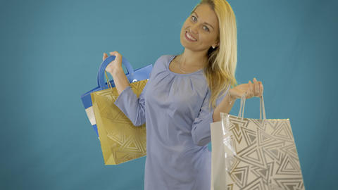 Happy young women with shopping bags spinning and smiling. Isolated solid blue Footage