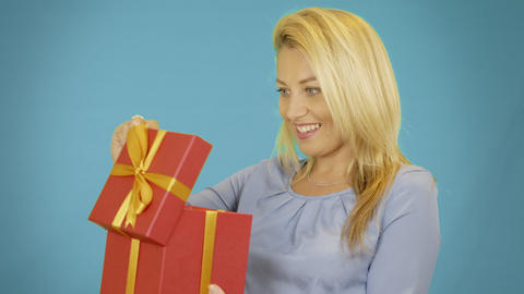 Wondered cute blonde young woman opening red gift box over blue background Footage