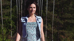 Portrait. The girl is walking along the rope bridge and looks beautifully at the Footage