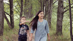 Cute happy little girl and boy running holding hands smiling. Brother and sister Footage