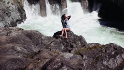 Beautiful girl posing sitting on the rocks. Behind her falls waterfall Footage