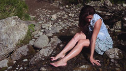 Beautiful girl is sitting on the stones. The stones run through the water. The Footage