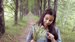 Portrait. A Little beautiful girl is walking on nature holding a bouquet of Footage