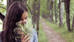 Portrait. A sweet beautiful little girl sniffs a bouquet of flowers while Footage