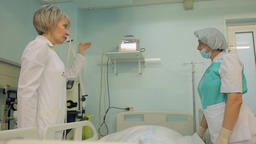 A female nurse and a female doctor visit a patient and discuss his condition Footage