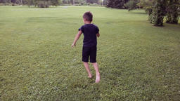 A little happy boy runs quickly across the grass bouncing in a happy mood Footage