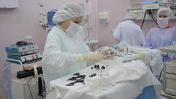 A team of medical doctors prepare surgical endoscopic instruments for Footage