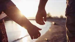 two Lovers Joining Hands. Detail Silhouette of Man and Woman holding hands over Footage