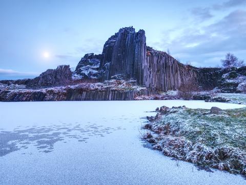 Peak of basalt pillars covered by snow, frozen pool. Full moon in blue sky in Photo