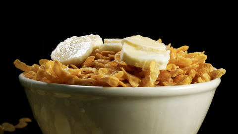 A bowl of cornflakes rotates against black background Footage