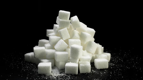 A pile of sugar pieces rotates against a black background Live Action