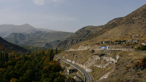 cargo truck moving on asphalt serpentine road thru the mountains. Beautiful Footage
