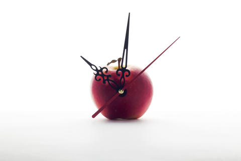 apple and clock hands on white background Photo