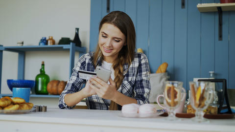 Smiling woman doing online shopping using smartphone and credit card while have Footage