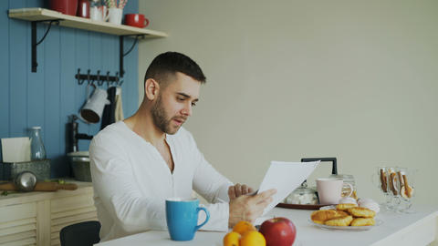 Handsome man recieve good news reading letter in the kitchen while have Footage