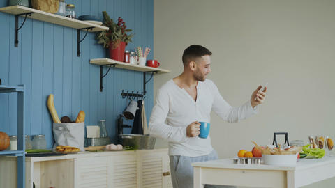 Cheerful happy man dancing and singing in kitchen while using his smartphone at Footage