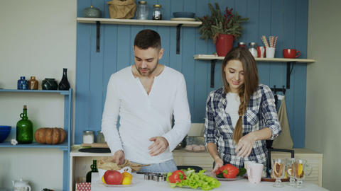 Happy young couple in the kitchen. Attractive dancing man cooking while his Footage