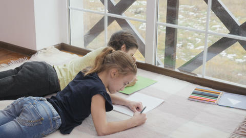 Two cute girls lays on floor and drawing Footage