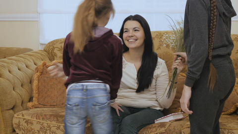 Two little daughters gives a bouquet of flowers to their mother Footage