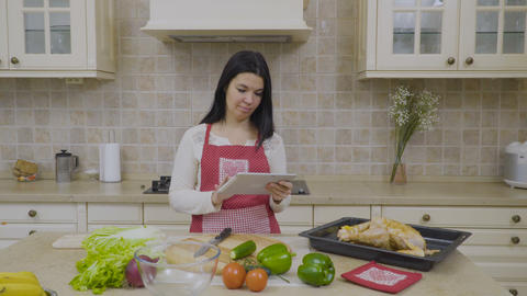 Modern woman looks the recipe of dinner at the tablet Footage